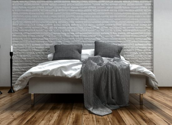 Unmade grey and white bed in a modern loft with two candelabras alongside on a wooden floor with textured brick wall, 3d rendered illustration