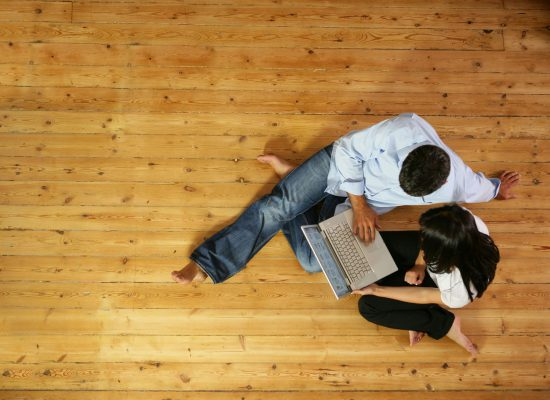 couple assis sur parquet avec ordinateur portable