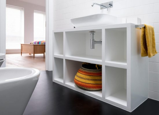 Contemporary white painted MDF bathroom unit, with colourful African bolga basket and black vinyl flooring