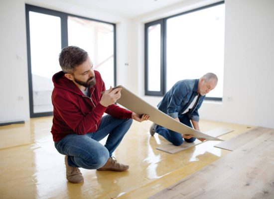 A rear and top view of mature man with his senior father laying vinyl flooring, a new home concept.