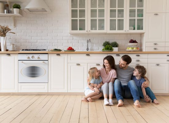 Happy parents with children sitting on warm wooden floor in modern kitchen, smiling father and beautiful mother hugging little cute daughter and son, family enjoying weekend at home together