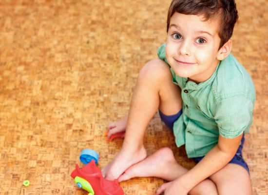 Boy playing with toys on the warm clean floor at home. Cork floor.