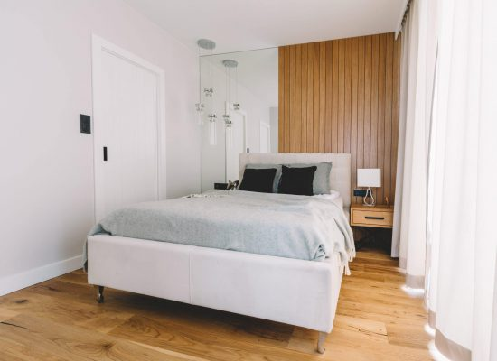 Small cozy bedroom with comfortable bed and wooden floor. Clean modern interior design