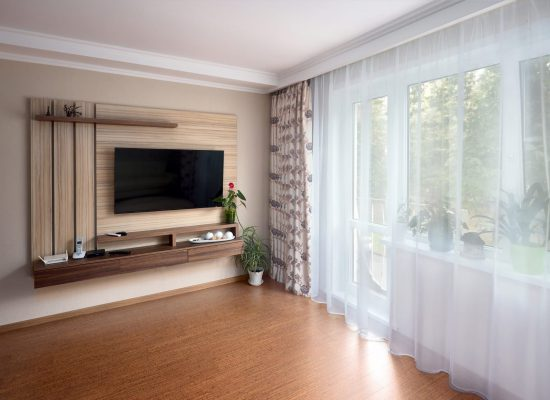 Modern apartment living room with large TV over wooden cabinet cork floorboards and glass door to balcony. Real room of real estate, residential house.