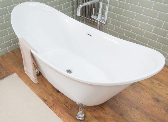 An oval bathtub in a bathroom with laminate flooring in a loft style house