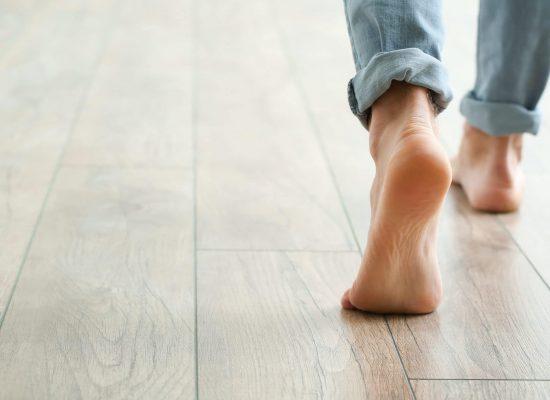 Man walking on new laminate flooring at home